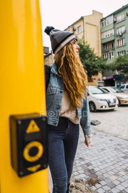 Young woman in hat and denim outfit looking pensive while walking at street. — Stock Photo