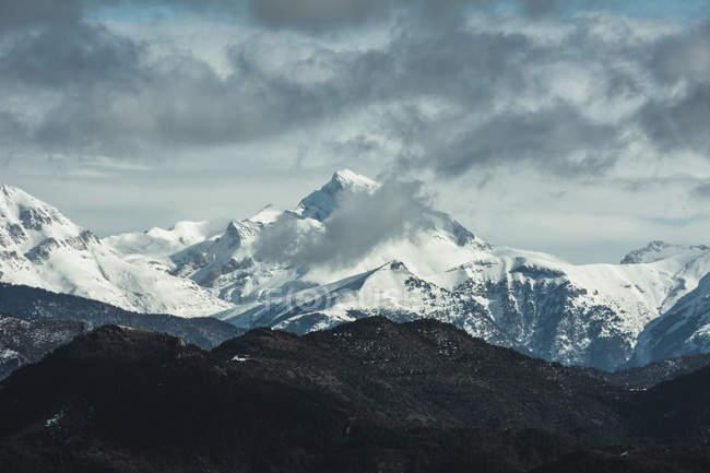 Panorama mozzafiato delle montagne coperte di neve sotto il cielo nuvoloso . — Foto stock