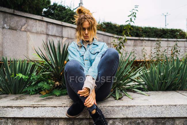 Jovem garota séria em jeans posando em concreta cerca no jardim — Fotografia de Stock