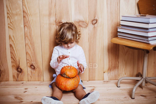 Charming boy sitting on floor with stacked pumpkins on knees — Stock Photo