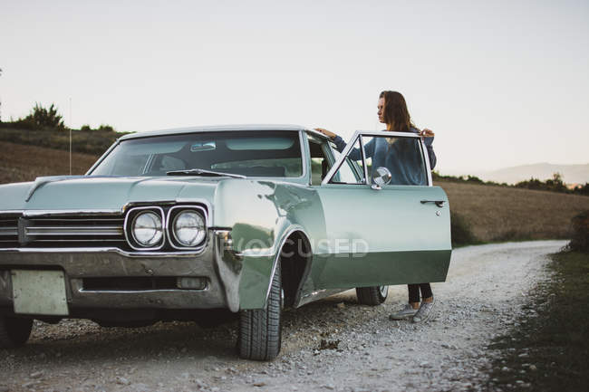 Woman opening door of retro car on background of field with dry grass. — Stock Photo