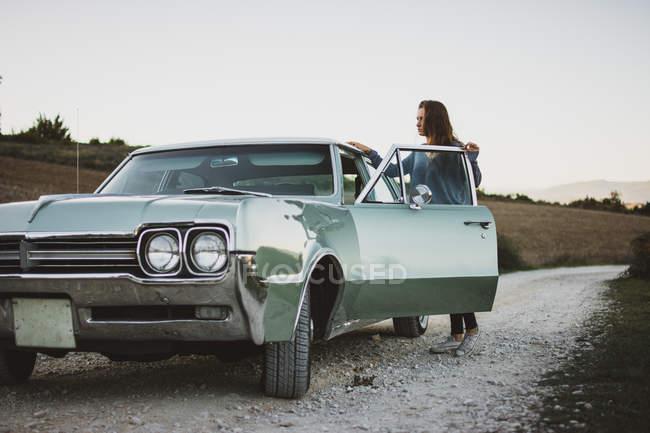 Женщина открытия двери ретро автомобиля на фоне поля с сухой травой — стоковое фото