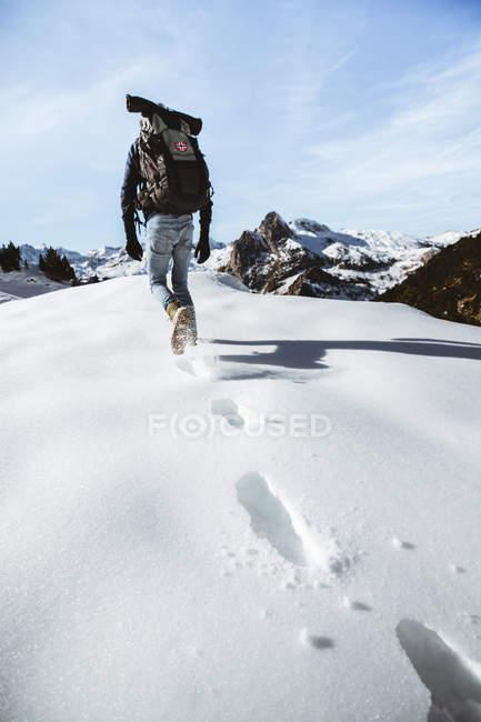 Visão traseira do homem com mochila andando em montanhas nevadas à luz do sol . — Fotografia de Stock