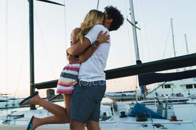 Jeune couple aimant embrasser sur la jetée avec des yachts sur fond . — Photo de stock