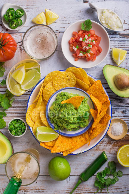 Wooden table with guacamole snack and nachos — Stock Photo