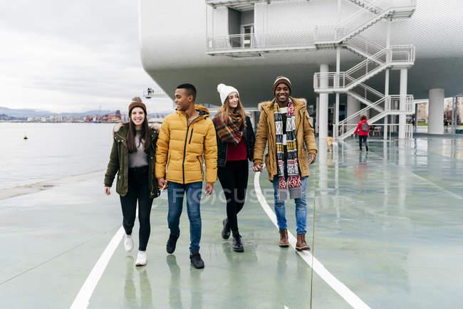 Счастливые пары держатся за руки и ходят по гавани — стоковое фото