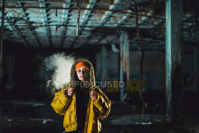 Young woman in yellow jacket in abandoned building — Stock Photo