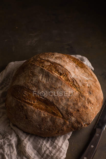 Frisch gebackenes Brot auf dunklem Tisch — Stockfoto