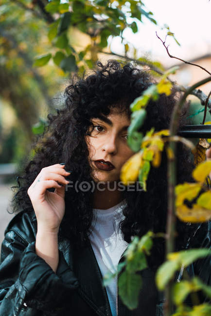 Pretty curly brunette woman posing at autumn leaves in park. — Stock Photo