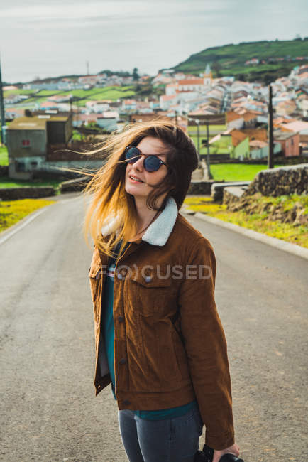 Stylish young woman in sunglasses standing on road on background of coastal town. — Stock Photo