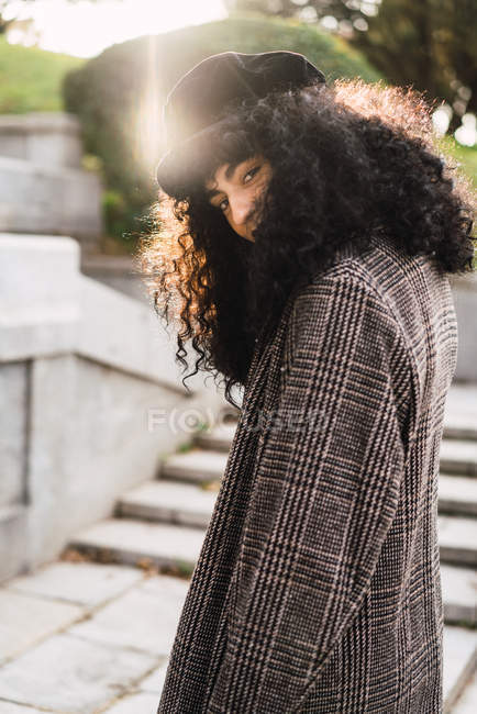 Pretty stylish woman walking in park and looking at camera — Stock Photo