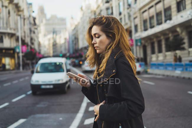 Вид збоку вродлива жінка, стоячи на вулиці і перегляду смартфон. — стокове фото