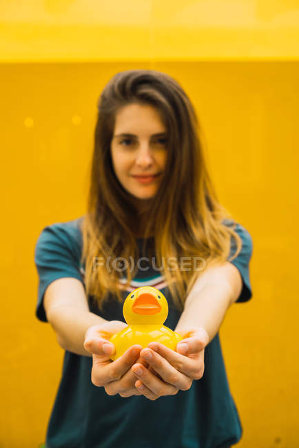 Charming woman outstretching hands with rubber duck on background of yellow wall — Stock Photo