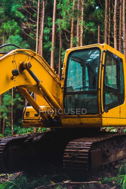 Gelber Traktor mit im Dreck auf dem Hintergrund grüner Bäume im Wald. — Stockfoto