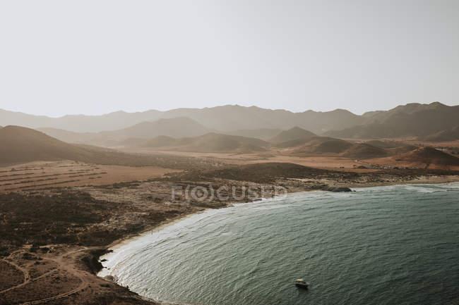 Переглянути на прибережній височини і заспокоїти океану в бухті з Маленька човен Вітрильна — стокове фото