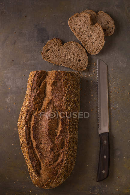 Still life of freshly baked bread loaf and slices with knife — Stock Photo