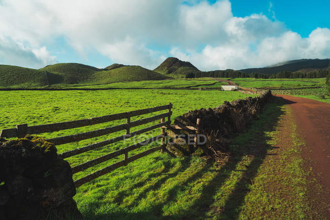 Blick auf grüne Wiese mit Zaun und Hügeln im sonnigen Tag. — Stockfoto