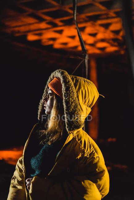 Портрет молодой женщины в желтой куртке, глядя через плечо прочь — стоковое фото