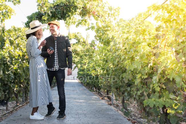 Happy young interracial couple walking in sunlit vineyard — Stock Photo
