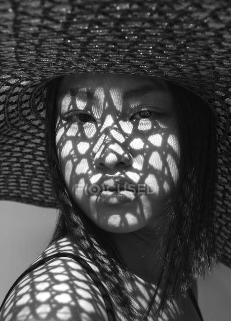 Asian woman in big hat and shadows on face — Stock Photo