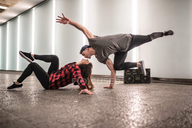Young happy couple dancing break dance on street and giving