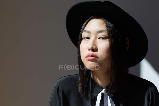 Stylish woman in hat looking at camera — Stock Photo