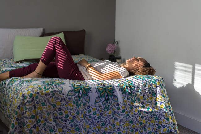 Side view of young cheerful woman lying on bed in shadows from blinds and relaxing. — Stock Photo