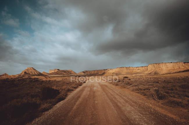 Estrada reta na paisagem do deserto sob forte cloudscape — Fotografia de Stock