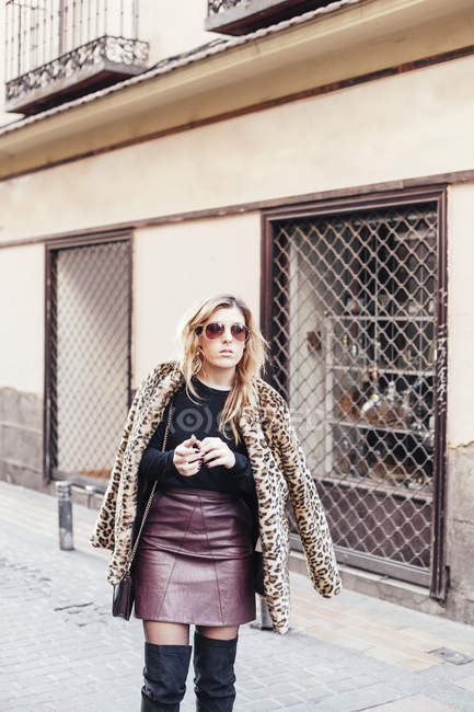 Portrait of young blonde woman wearing leather skirt and fur coat at street scene — Stock Photo