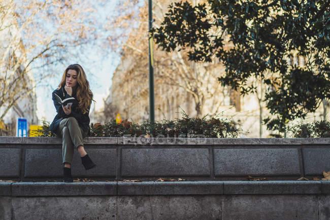 Frau sitzt und liest Buch im park — Stockfoto