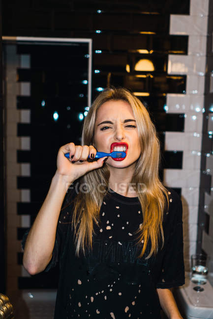 Young  blonde woman posing with brushing teeth and looking at camera. — Stock Photo