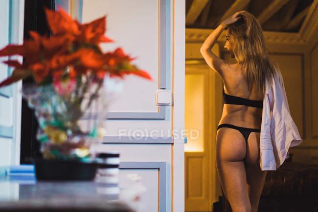 Rückansicht des blonden Frau in Dessous posieren in Tür. — Stockfoto