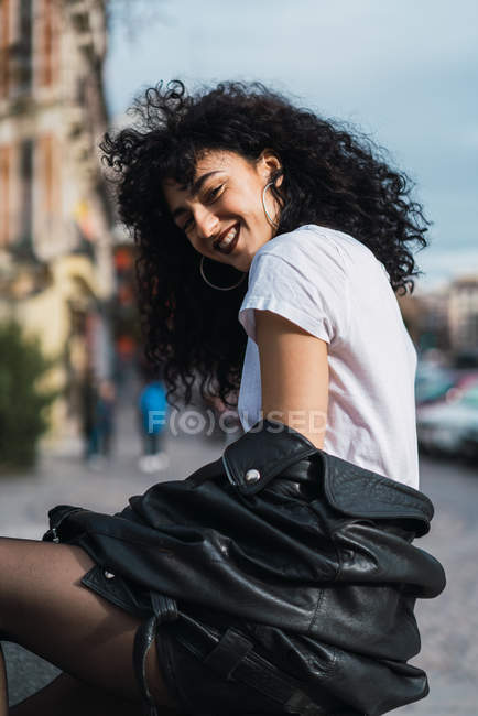 Cheerful curly woman posing in city — Stock Photo