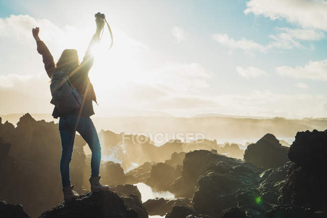 Cheerful woman with camera on cliff — Stock Photo