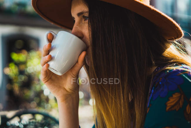 Portrait of woman drinking coffee at cafe terrace — Stock Photo