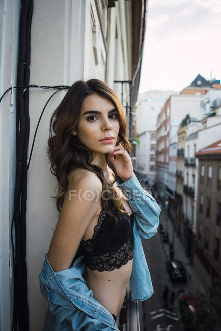 Brunette woman in lingerie posing on balcony and looking at camera — Stock Photo