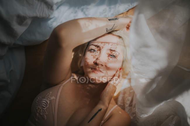 Desde arriba la vista del joven acostado en la cama con la sombra de la cortina en la cara. - foto de stock