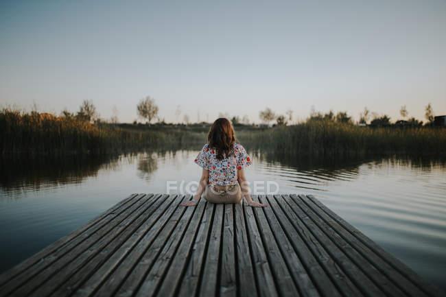 Vue arrière de la femme assise sur une jetée en bois au lac — Photo de stock