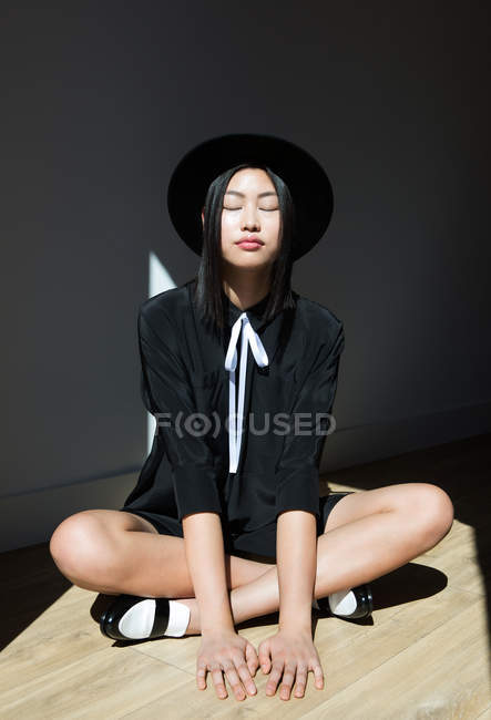 Stylish woman sitting on sunlit floor with eyes closed — Stock Photo