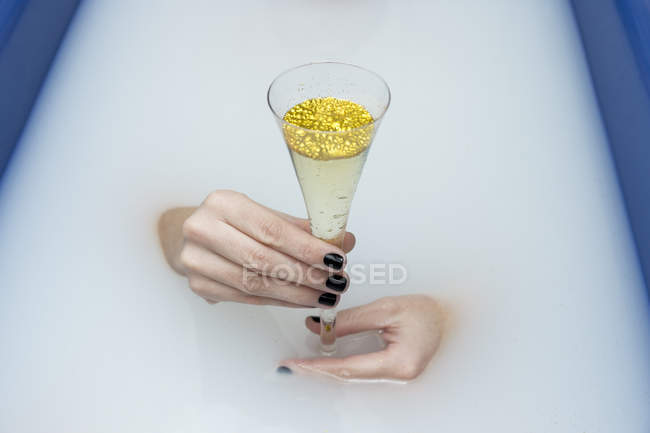 Female hands in bathtub with milk holding  glass of champagne with golden glitter — Stock Photo