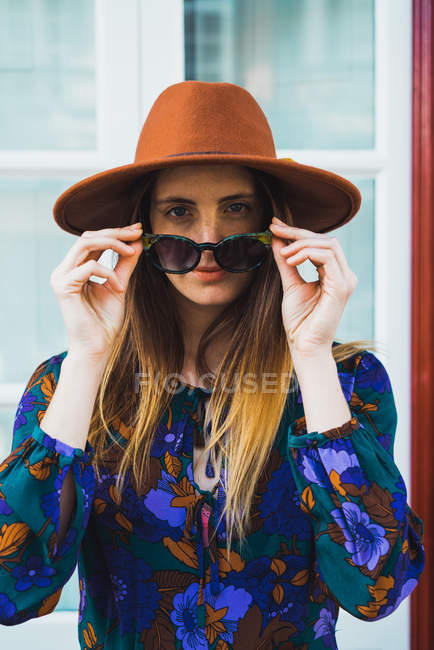 Allegro donna elegante in cappello in posa con occhiali da sole — Foto stock