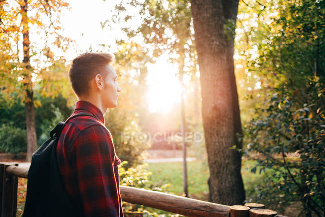 Young man standing on bridge at sunny park — Stock Photo
