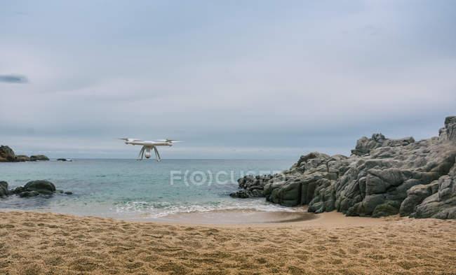 Drone de Quadcopter dans les airs à la plage de sable — Photo de stock