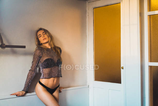 Blonde woman in panties posing at wall with eyes closed — Stock Photo