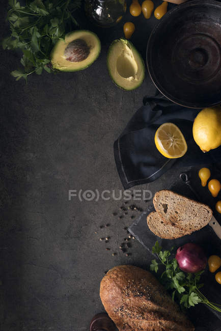 From above empty bowl and avocado with lemon and bread on dark background. — Stock Photo
