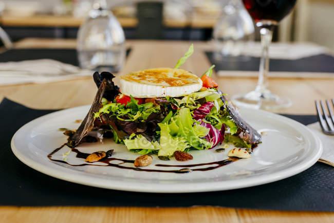 Chiuda sulla vista di piatto di insalata di verdure con formaggio, carne di maiale e noci — Foto stock