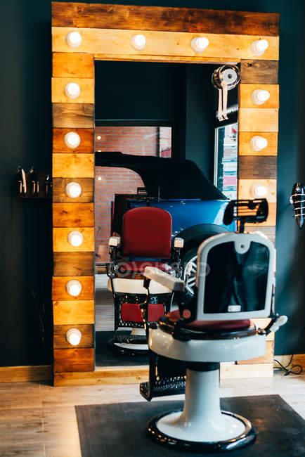 Chaise vide placée au miroir avec éclairage dans le salon de coiffure . — Photo de stock