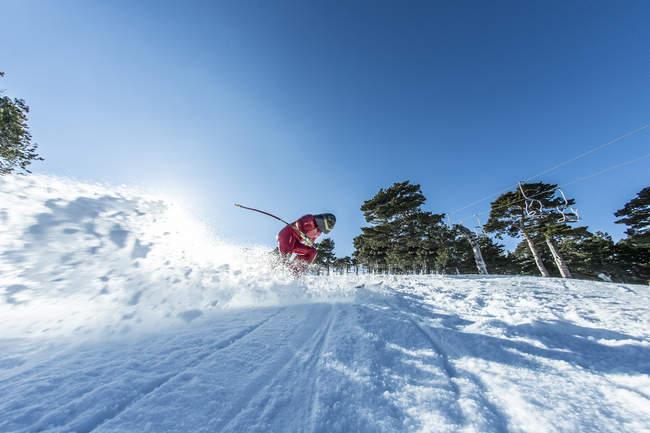 Homem praticando velocidade esquiar numa encosta sob céu azul — Fotografia de Stock