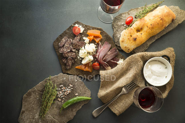 Сверху вкусные мясные закуски с хлебом и овощи на каменные плиты — стоковое фото