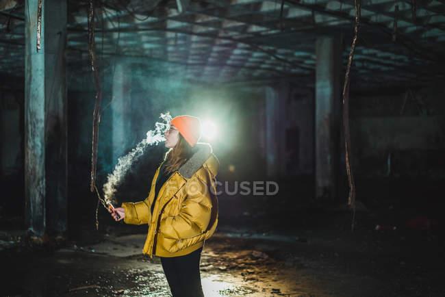 Mujer vapeando en edificio abandonado en edificio abandonado - foto de stock